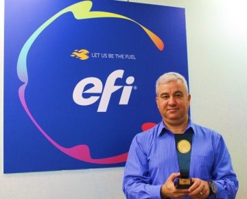 Ernande Ramos, director de ventas para América Latina de EFI, muestra el premio Proveedor Premium en Conversión Digital